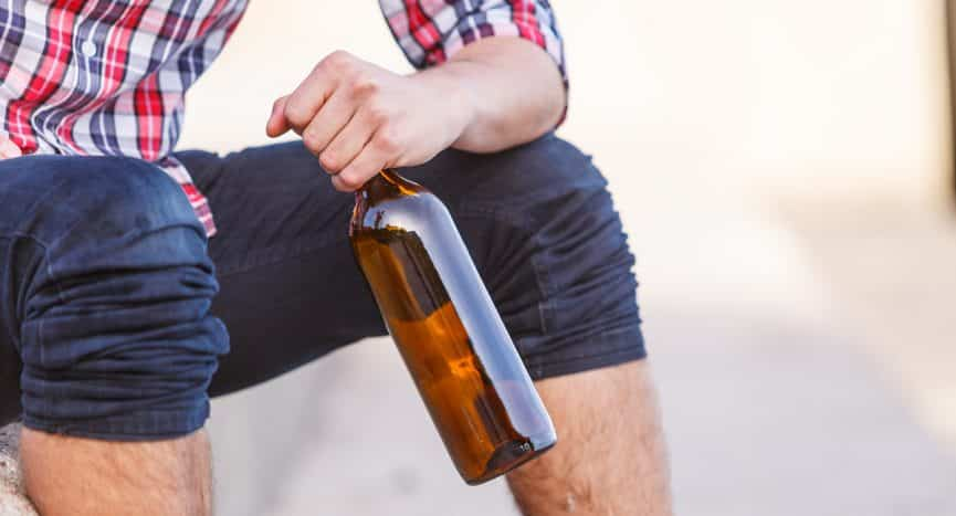 man in shorts holding beer bottle