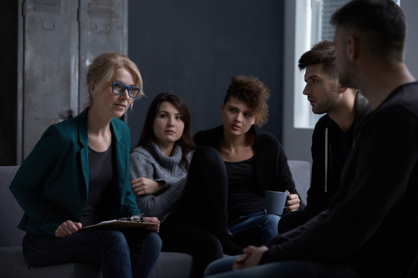 Group of people listening to a woman with blue rimmed glasses