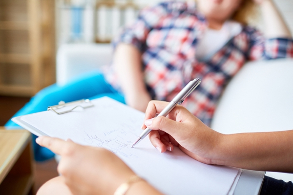Woman sitting with clip board and pen listening to another woman