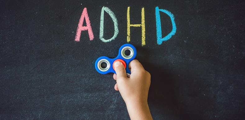 The letters ADHD printed on a chalk board