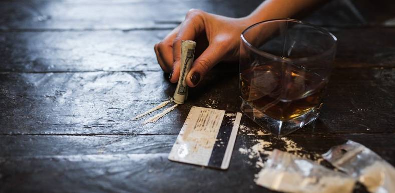 person preparing a line of cocaine next to glass of alcohol