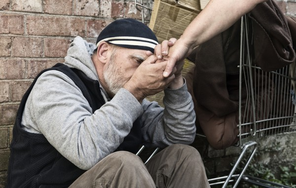 Homeless man sitting with his back to the wall with someone reaching out to them.