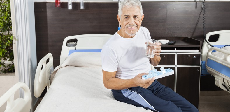 Man sitting on hospital bed taking medications
