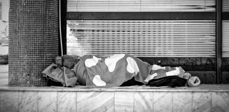 Person lying on the ground with a blanket.