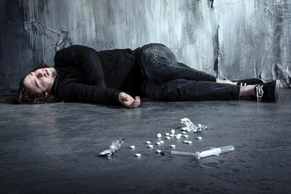 Person lying on the ground with drugs in front of him.
