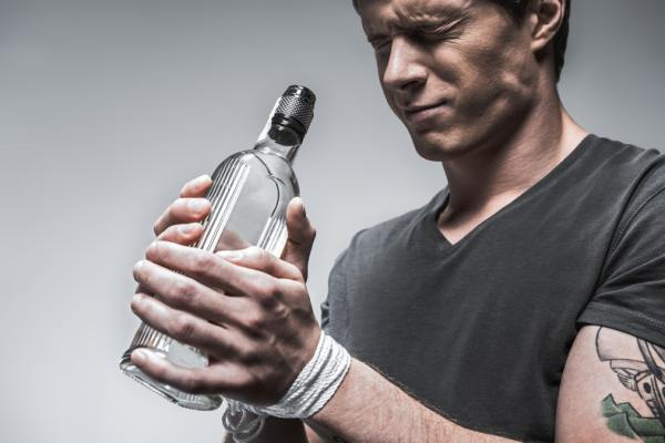 Man holding a bottle of alcohol squinting.