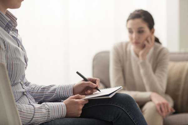 Woman sitting on a couch talking to a therapist who is writing in a notebook.