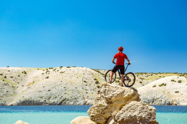 Person with a mountain bike on a rocky hill overlooking water.