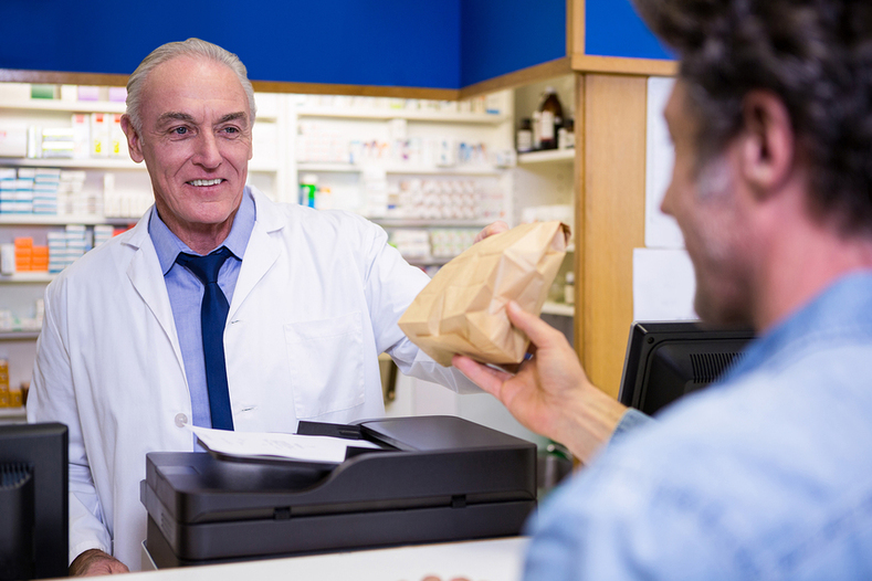 Pharmacist handing a customer a bag.