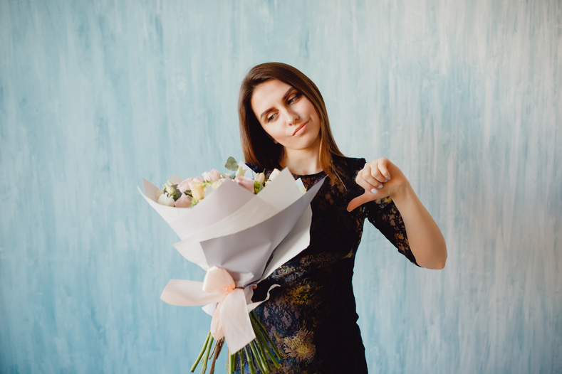 Woman holding a bouquet of flowers with a thumb down.