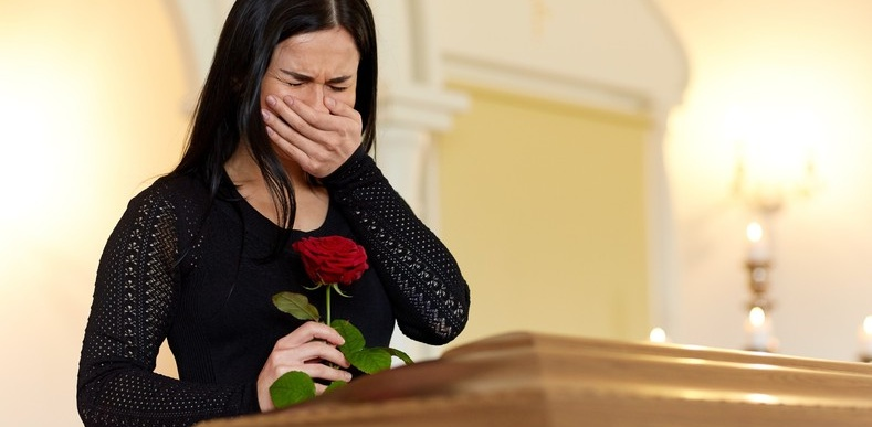 Woman crying over a casket