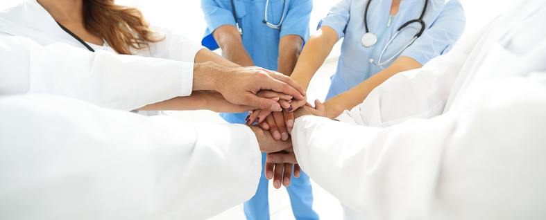 a group of medical professionals putting hands together
