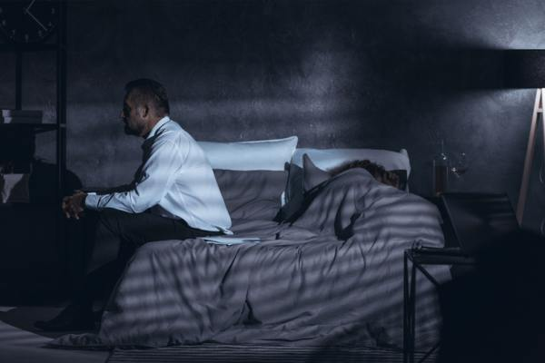 Person sitting on a bed in a darkened room.