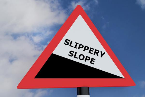 Black and white triangle shaped sign Slippery Slope.