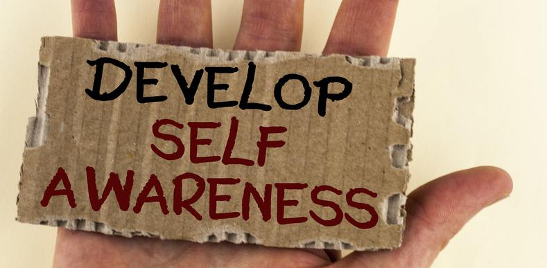 "Hand holding a sign ""Develop Self Awareness"""