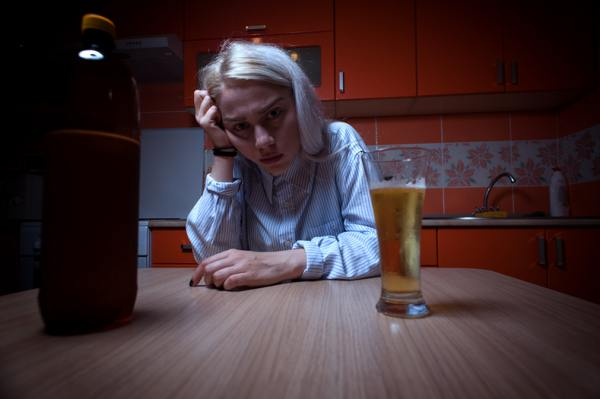 Woman sitting at a kitchen table staring at a glass of alcohol.