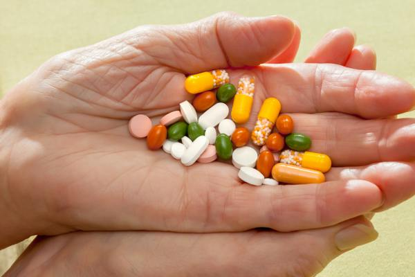 Person holding multiple pills in their hand.