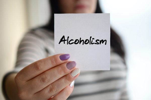 Woman holding a card with the word alcoholism on it.