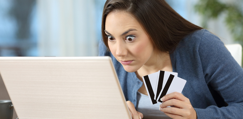 Woman looking at a laptop with credit cards.