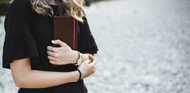 Woman holding books in her arms.