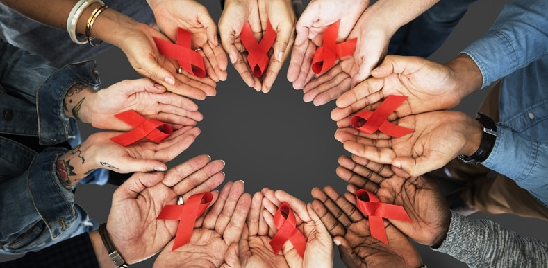 circle of hands holding red ribbons