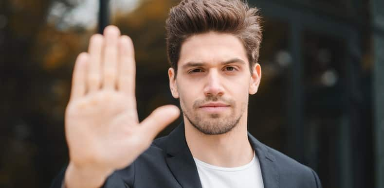 man holding his hand up signaling to stop