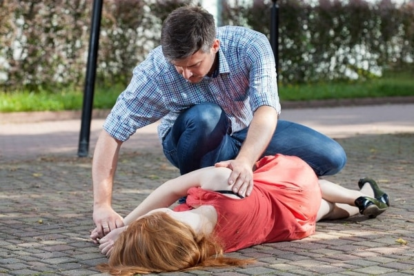 Man checking woman lying on the ground