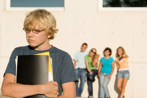 Male student standing alone with a group of students in the background.