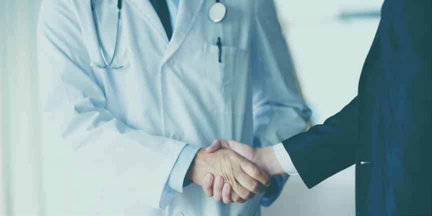 A doctor and an insurance representative shake hands and discuss rehab treatment