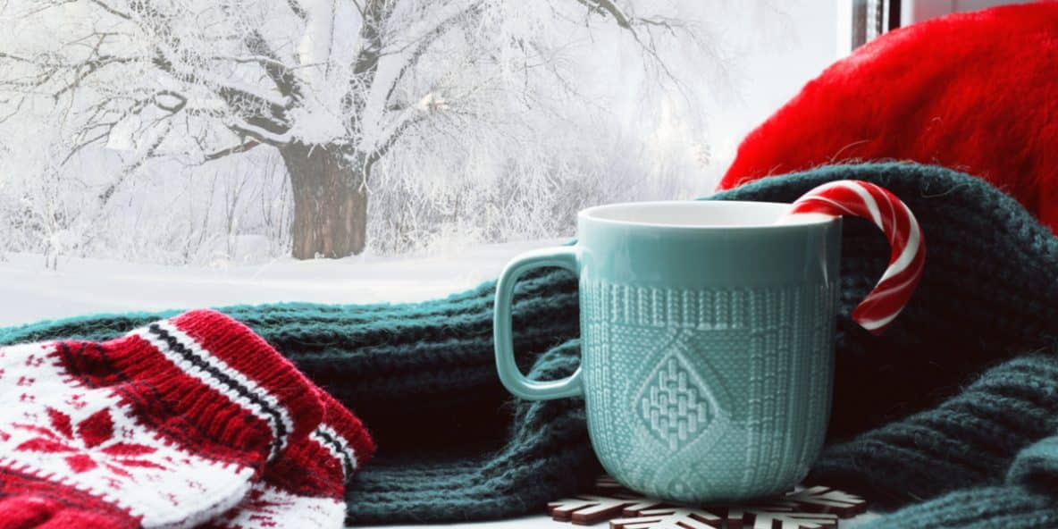 A cup of coffee next to winter clothes in the snowy weather where opioid overdoses are high