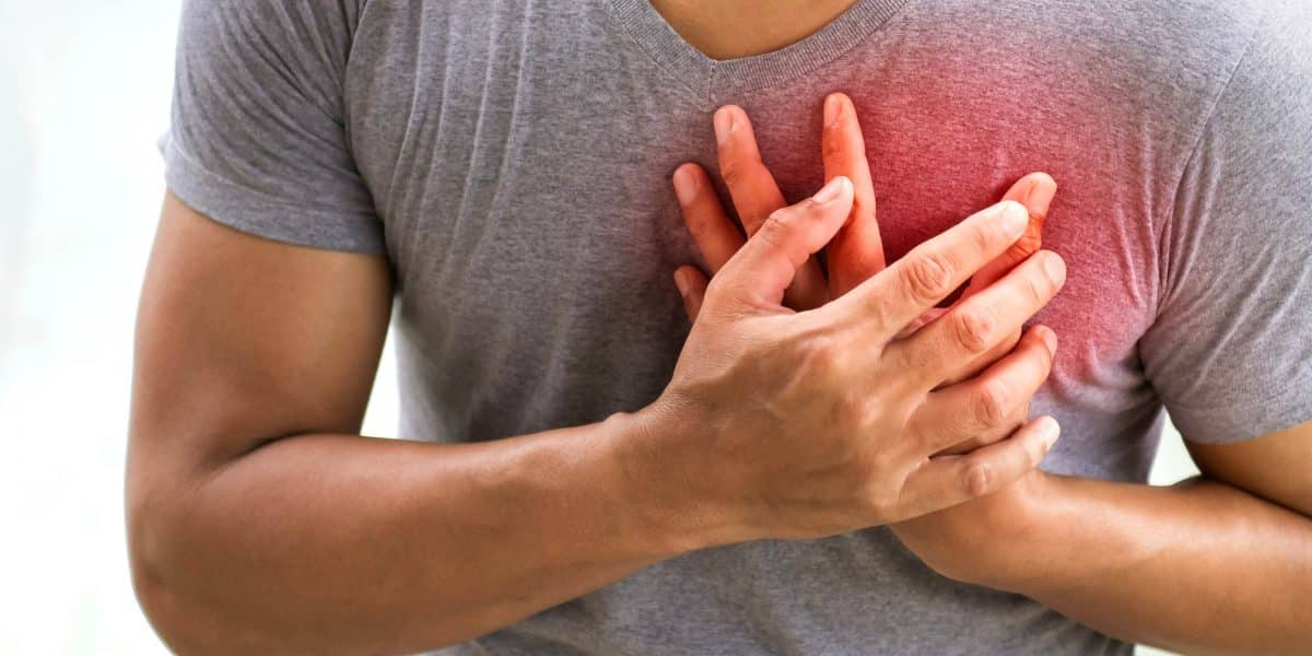 man gripping his chest after overdosing on amphetamines