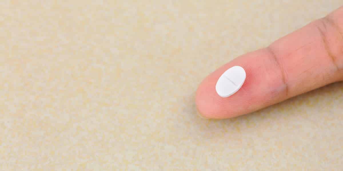 person holding benzodiazepine pill on their finger tip