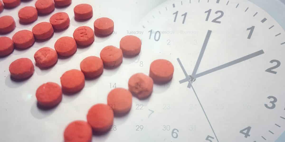 amphetamine pills overlaying image of clock and calendar