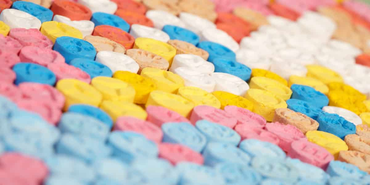 Colorful ecstasy pills lined up in rows