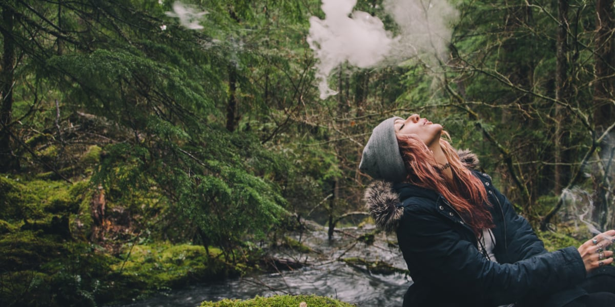 girl smoking a marijuana joint in a Washington forest