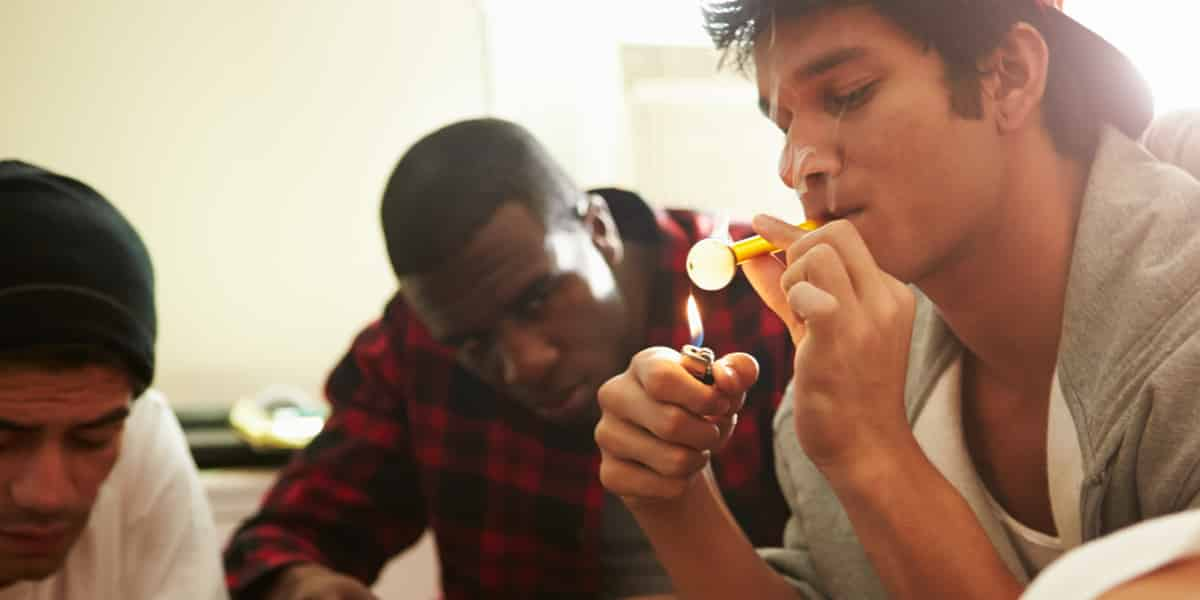 A group of guys smoking meth out of a glass pipe