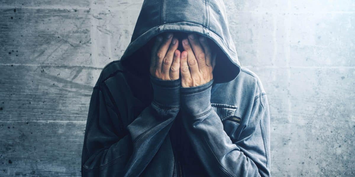 person in hoodie covering face while experiencing withdrawal symptoms