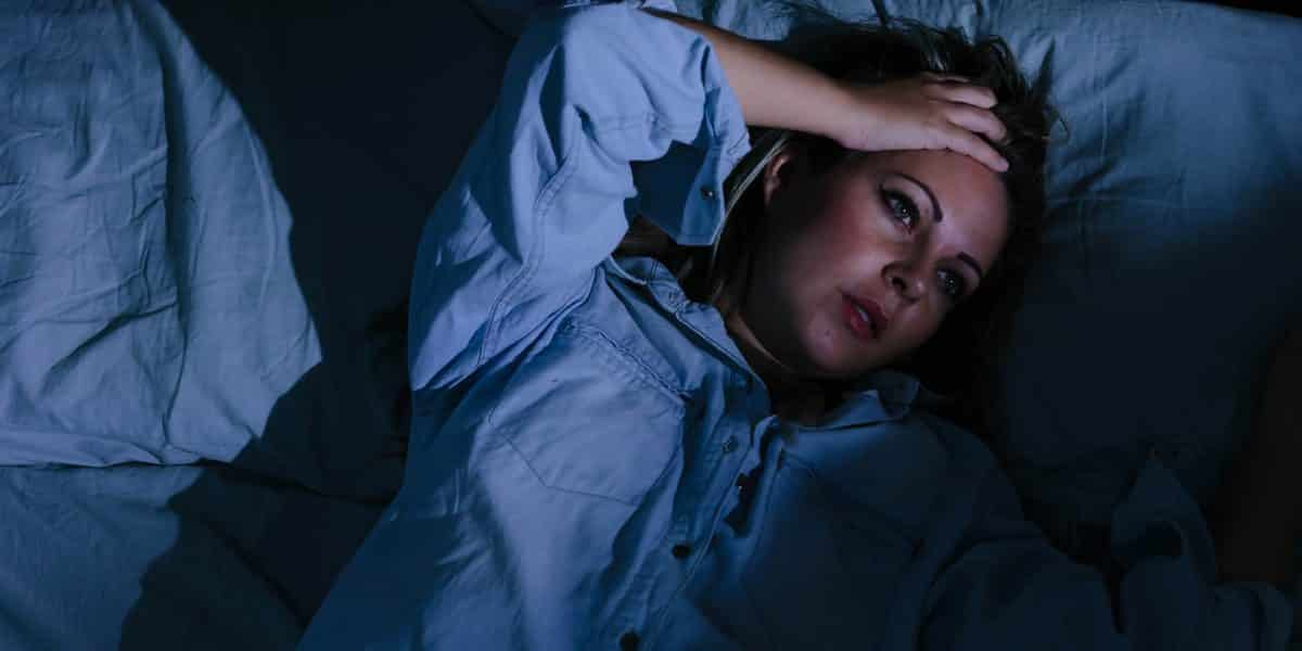 woman laying awake in bed after overdosing on Vyvanse