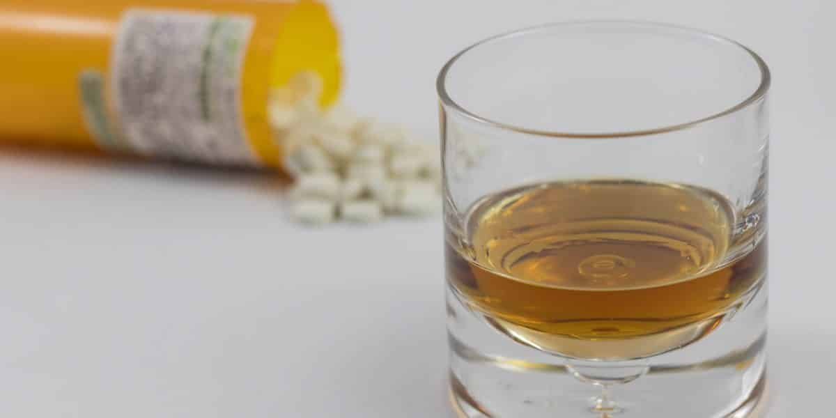 Klonopin pills spilling out of a prescription bottle next to a glass of alcohol
