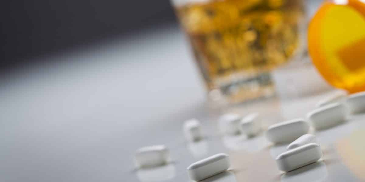 spilled tramadol pills next to alcoholic drink