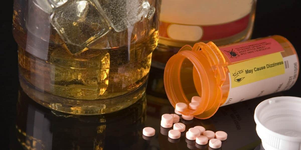 Vyvanse pills spilling out of a prescription bottle next to a glass of alcohol