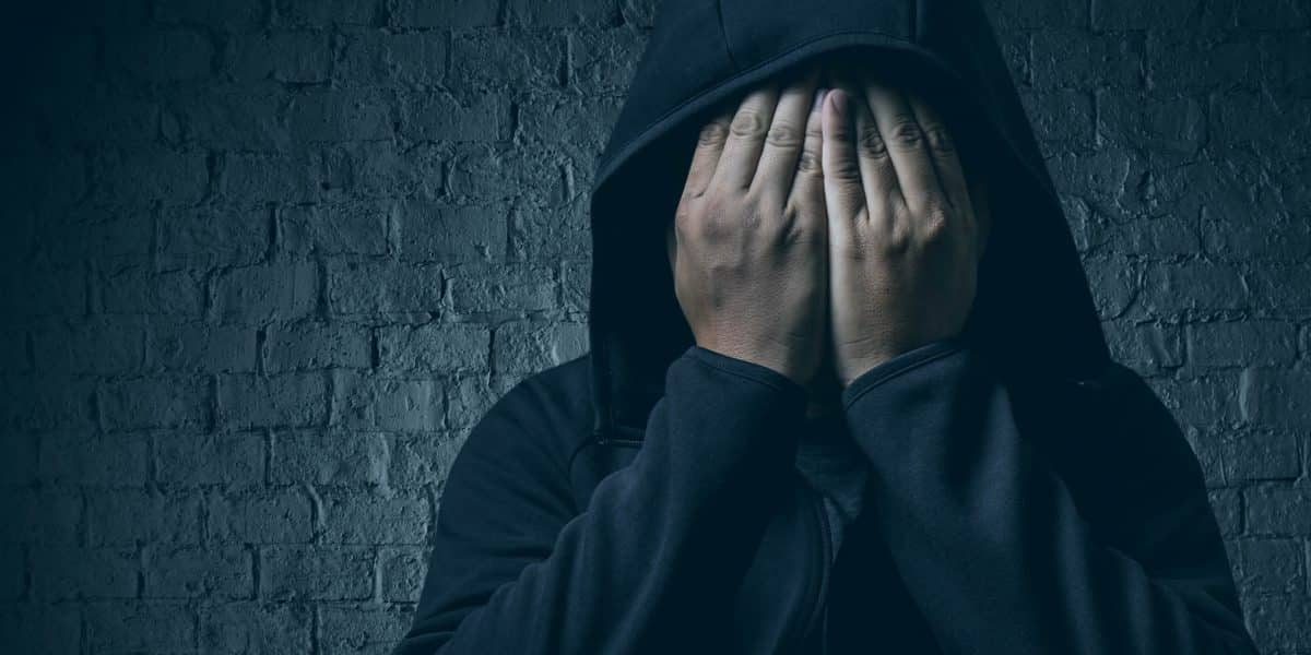 person in hoodie covering face as they experience Tramadol withdrawal
