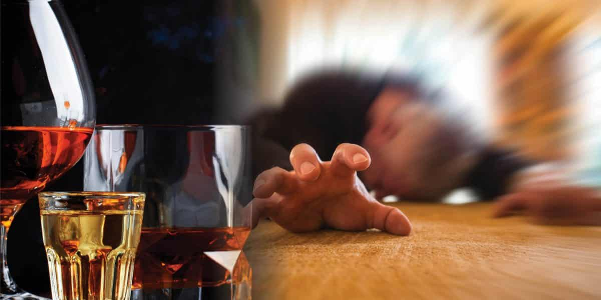 person passed out reaching for glass of alcohol