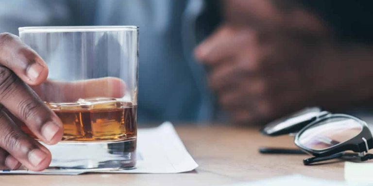 employee, hand grasping glass of alcohol with head down on work desk